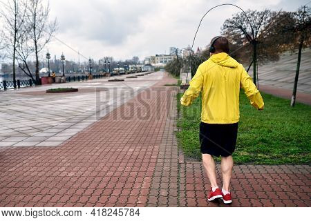 The Athlete Jumps On A Racecar In The Morning In A Sports Jacket And Shorts. The Embankment Is Made