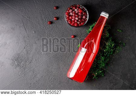 Cranberry Juice In A Glass Bottle On A Black Stone Background, Cranberry Berries, Green Moss, Top Vi
