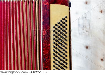 Antique Red 120 Bass Accordion.covered With Dust On Wooden Construction Background.