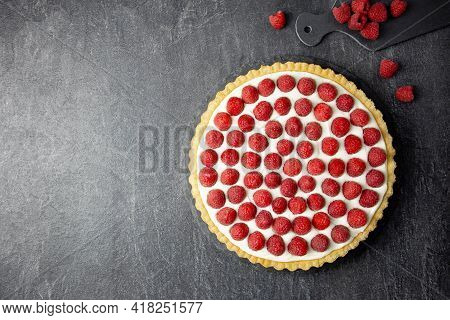 Delicious Raspberry Tart With Whipped Cream And Mascarpone On A Dark Concrete Background. Top View.