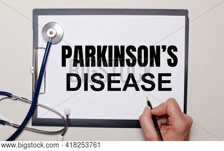 On A Light Background, A Stethoscope And A Sheet Of Paper, On Which A Man Writes Parkinson Is Diseas