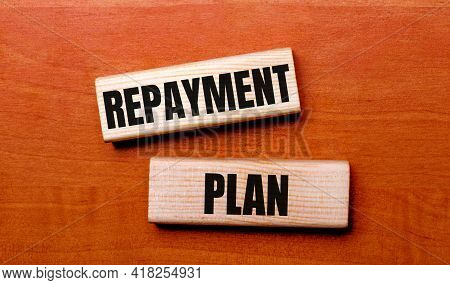 On A Wooden Table Are Two Wooden Blocks With The Text Question Repayment Plan