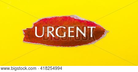 On A Yellow Background, A Sheet Of Red Paper With The Word Urgent
