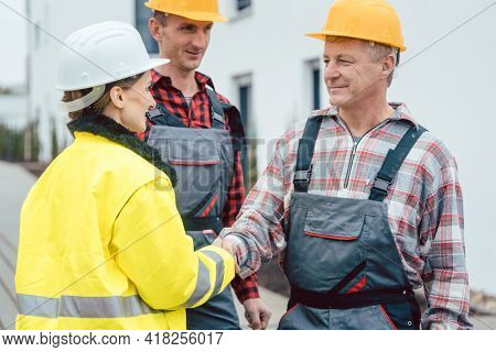 Builder and contractor on construction site shaking hands in acceptance