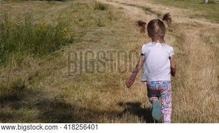 5s Little Girl Run Away By Country Road At Rural Landscape In Summer. Her Blonde Ponytails Jump In A