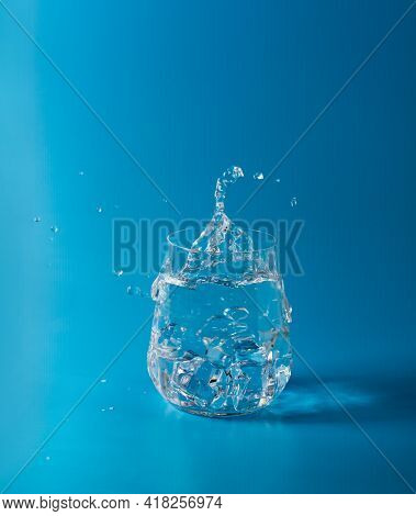 Crystal Clear Water With Ice In A Clear Glass Glass On A Blue Background. Splash And Splash