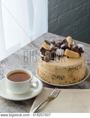 A Cup Of Tea On A Saucer And A Sponge Cake With Buttercream On The Stone Countertop. The Cake Is Dec