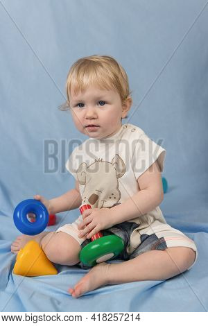 A Small Blue-eyed Blonde Child Sits On A Blue Background And Plays With Toys. Looking Away