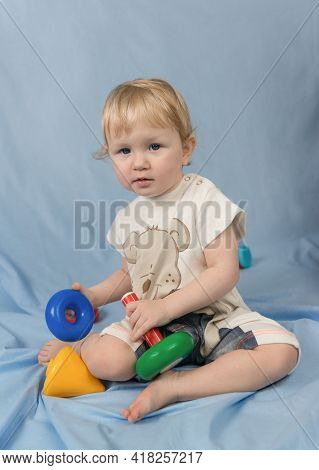 A Small Blue-eyed Blonde Child Sits On A Blue Background And Plays With Toys. Plastic Multi-colored
