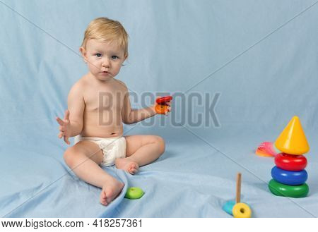 A Small Serious Blonde Girl In A White Diaper Sits On A Blue Background With A Wooden Pyramid. In Th