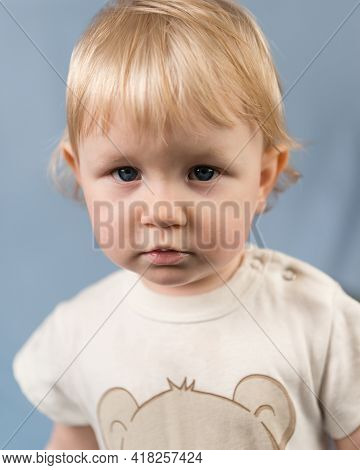 Close-up Portrait Of A Blonde Girl Aged 1 Year. The Serious Look Of A Blue-eyed Child