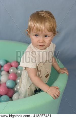 A Little Girl Stands In A Green Dry Pool With Plastic Colored Balls