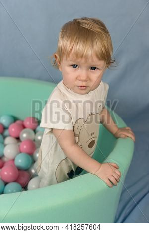 A Little Blonde Girl Stands In A Green Dry Pool With Plastic Colored Balls. Looking At The Camera