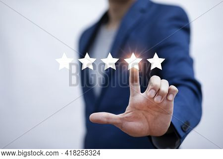 The Concept Of Placing Rating. Businessman Touching Technology On Five Star Excellent Rating On Blue