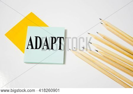 Adapt Word Written On A Yellow Piece Of Paper And White Background With Pencils Lying Next To It. Wo