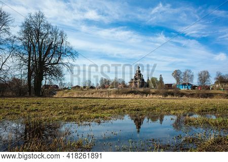 Suzdal, Church of the Transfiguration of Kozlyatevo reflecting in water on grass field in spring middle april, Monument of wooden architecture, Russian heritage architecture, Golden Ring of Russia