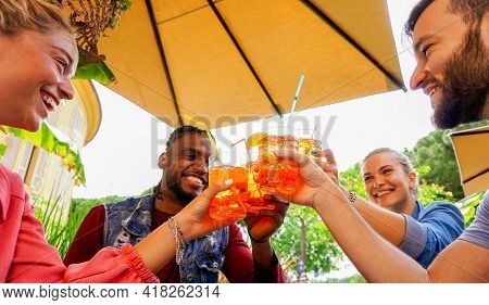 Group Of Young People Having Fun Outside In A Bar With Drinks In Summer - Friends Cheering With Cokt