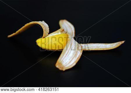 Banana Peel, Peeled Half A Banana On A Black Background,