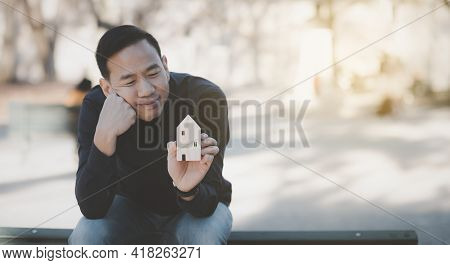 Asian Happy Man Hand Choosing Mini Wood House Model From Model On Wood Table, Planning And Buy Real