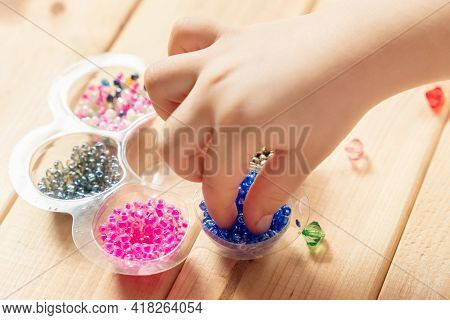 The Child Makes Jewelry With His Own Hands, Stringing Colorful Beads On A Thread