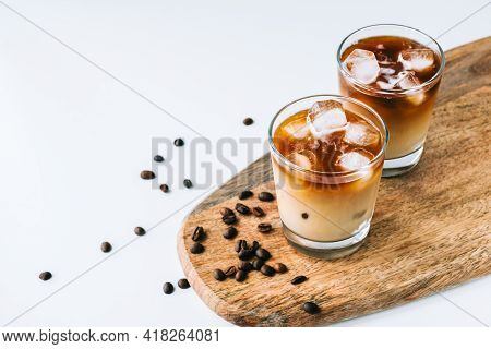 Ice Coffee In Glass With Milk And Ice Cubes, Coffee Beans On White Table.