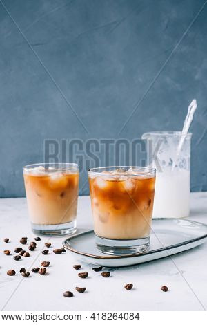 Ice Coffee In Glass With Milk Foam And Ice Cubes, Coffee Beans On White Table.