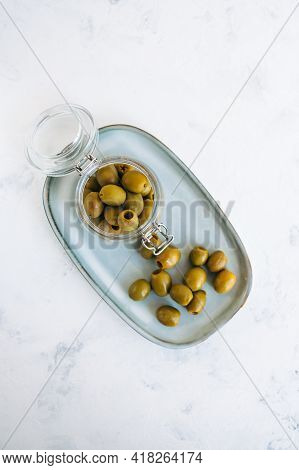 Jar With Green Olives On A Plate, Top View.