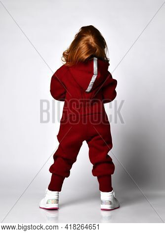 Rear View Of Little Red-haired Preschooler Girl Wearing Warm Tracksuit Sportswear With Hood And Whit