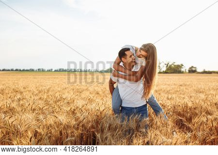 Happy Boy And Girl On The Background Of A Ripe Field With Wheat. A Loving Couple Hugging On A Sunny
