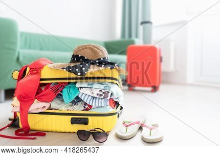 Suitcase Packed To Vacation, Open Yelow Luggage Full Of Clothes In The Room