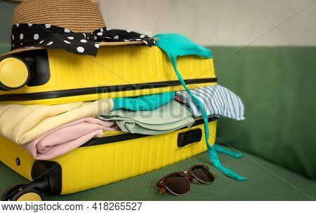 Travel. Packed Yellow Suitcase Full Of Vacation Items On The Sofa