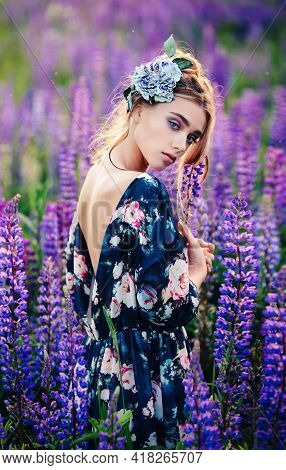Natural Beauty Woman With A Flower In Her Hair Walking In A Lupine Summer Flowers Field. Beauty Port