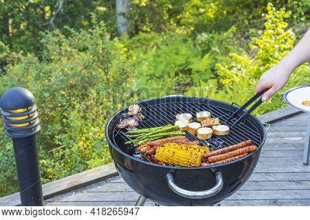 Close Up View Of Man's Hands Grilling Food On Coal Grill. Sweden.