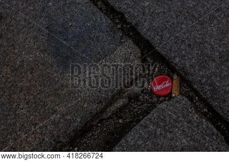 Pilsen, Czech Republic, 1.09.2019 - Red Coca-cola Bottle Cap On Old Stone Sidewalk. Coca-cola Is Mos
