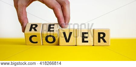 Recover Symbol. Concept Word 'recover' On Wooden Cubes On A Beautiful Yellow Table. Businessman Hand
