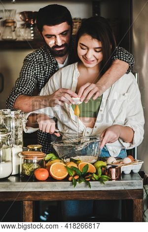 Young Caucasian Couple Hugging Baking Holiday Cake Together At Home