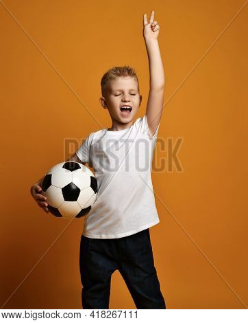 Happy Kid Boy In White Blank T-shirt Stands Holding Soccer Ball In Hand And Gestures V Victory Sign,
