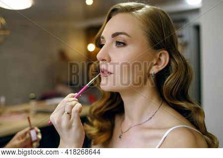 Make-up For A Beautiful Girl Is Done In A Beauty Salon. Master Stylist Applies Lipstick With A Brush