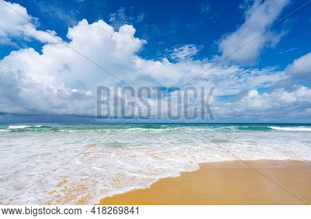 Beautiful Sandy Beach With Wave Seafoam Clashing On Sandy Shore Turquoise Ocean Water And Blue Sky W