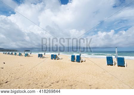 Summer Sandy Beach With Beach Chair And Wave Seafoam Clashing On Sandy Shore Turquoise Ocean Water A