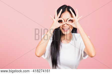 Portrait Asian Beautiful Young Woman Standing, She Made Finger Ok Symbol Sign To Agree Near Eyes Loo