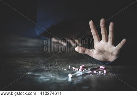 Man Ddict With A Syringe Using Drugs On The Floor . Drugs Addiction And Withdrawal Symptoms Concept.