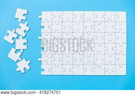 Unfinished White Jigsaw Puzzle Pieces On Blue Background, The Last Piece Of Jigsaw Puzzle, Copy Spac