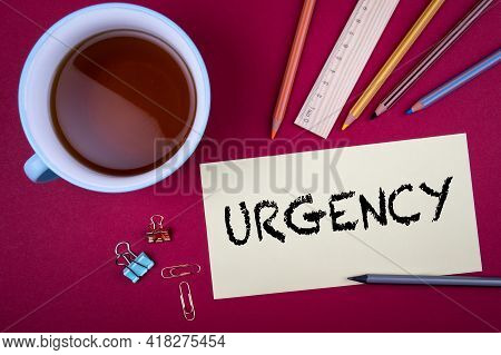 Urgency. Tea Cup And Office Supplies On A Red Table