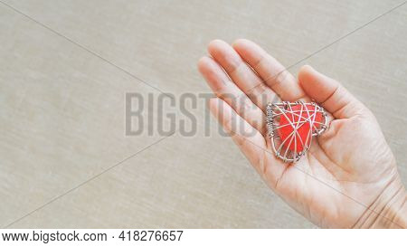 Red Heart In Wire Mesh On Human's Hand With Blurred Light Brown Background For Healthy Heart, Heart