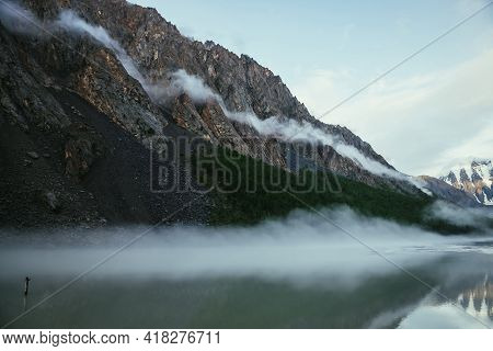 Scenic Alpine Landscape With Long Low Cloud On High Rockies In Sunlight Above Green Mountain Lake In