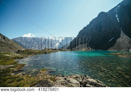 Sunny Relaxing Landscape With Azure Glacial Lake In Sunlight. Meditative Ripple And Many Reflected L