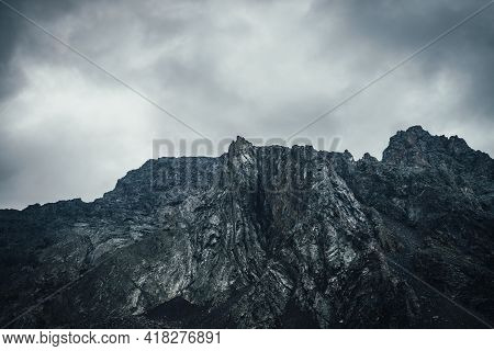 Dark Atmospheric Landscape With Rocky Mountain Wall Under Gray Cloudy Sky. Rocky Pinnacle In Lead Gr