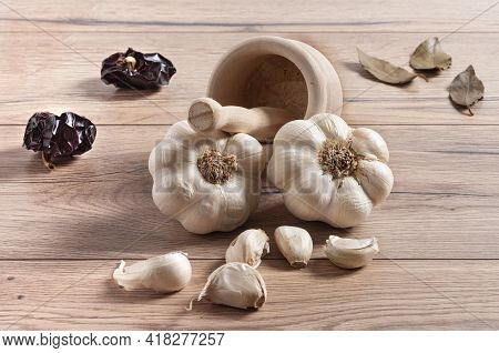 A Closeup Of Garlic Bulbs And Cloves On A Wooden Table