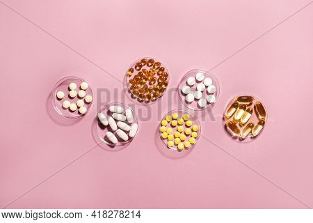 Vitamins Capsules And Pills On Pink Background, Top View, Copy Space. Food Supplements: Fish Oil, Om